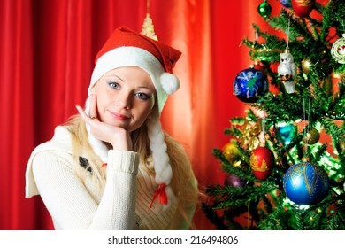 Beautiful blonde in a red cap with Christmas tree.  Christmas photo of blonde in red cap. New Year's holidays and Christmas tree..