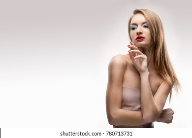 The beautiful blonde red lips smiling girl touches by fingers face and a neck and looks sideways. Isolated on a white background. Healthy clean leather. Manicure - red nails. Copy space.