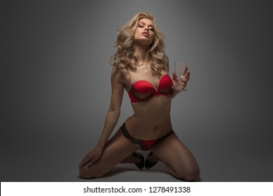 Beautiful blonde in red underwear holding empty glass kneeling on gray background