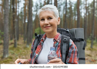 Beautiful blonde retired female spending vacations outdoors, walking in forest with rucksack behind her back, holding plastic bottle of water, drinking. Refreshment, rest and active lifestyle