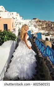Beautiful blonde runaway bride in white wedding dress on the island of Santorini in Greece with amazing views
