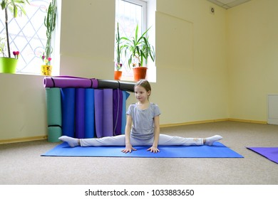 Beautiful blonde schoolgirl sitting on floor on cross twill. Hair in child neatly combed, dressed comfortable sportswear and sits on blue mat for fitness. Concept of need for children to develop