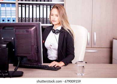 Beautiful blonde secretary at her work place at the office