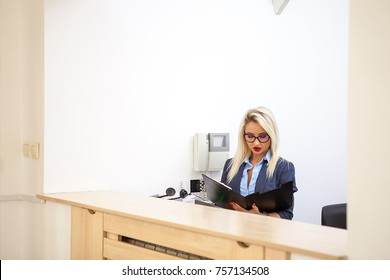 Beautiful blonde secretary looking at folder with documents in the reception area of an office