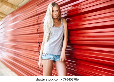 Beautiful blonde sexy young tanned woman posing on red background on the street in summer