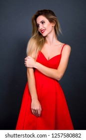 Beautiful blonde sexy young woman in a red dress on a gray background