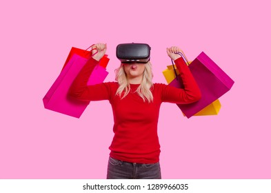 Beautiful blonde with shopping bags and vr glasses on pink background, sticking tongue out ; online shopping