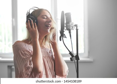 Beautiful blonde singer girl in headphones in home recording studio sings a song into a microphone, laughs and smiles close-up