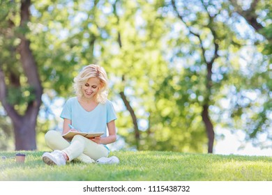 A beautiful blonde is sitting on the grass and writes in a diary next to a glass with a coffee / copy space