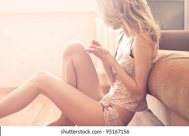 beautiful blonde sitting in a room filled with light