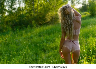 Beautiful blonde slim girl with a nice ass wearing pink lingerie and a ribbon on her sexy body stands with her back turned in the park. Summer lifestyle photo. Commercial design. Copy space.