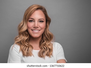 Beautiful blonde is smiling. Studio photo of a young attractive woman on a gray background.