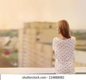 Beautiful blonde stands on the edge of the roof
