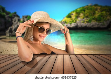 Beautiful blonde with straw hat and sunglasses in a tropical island background