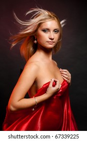 beautiful blonde in the studio on a black background with red cloth