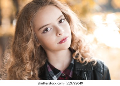 Beautiful blonde teenage girl 12-14 year old wearing leather jacket outdoors. Looking at camera. Autumn season.
