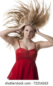 Beautiful blonde teenage girl with flying hair in a red dress