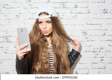 Beautiful blonde teenage girl in white cap, leather jacket taking a selfie on smartphone, posing, making a kissy face, standing against white brick wall. Copy space, retouched, no filter.