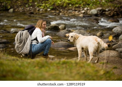 Beautiful blonde teenager girl with backpack in hiking bots and warm clothes, plays with her golden retriever friend outdoor, next to a river.