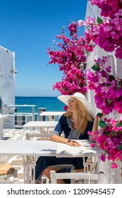 Beautiful, blonde tourist enjoys her summer vacation on a typical Greek island in the Cyclades with whitewashed houses and colorful flowers, Greece