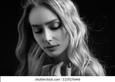 beautiful blonde transgender with bare shoulders on black background
