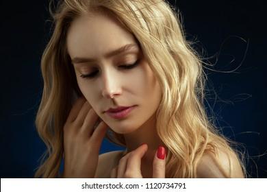 beautiful blonde transgender with bare shoulders on dark blue background