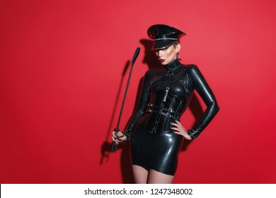 Beautiful blonde vamp officer uniform mistress dominatrix bdsm woman in glamour latex dress, corset, officer hat and black leather fetish harness posing in sex shop red room