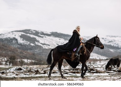 Beautiful blonde Viking in a black cape on horseback, mountain snow in the background