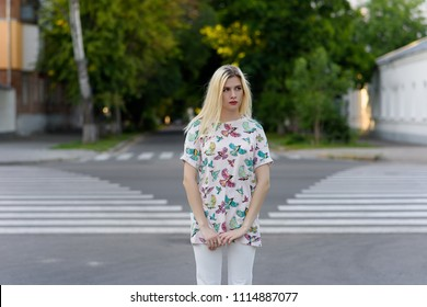 Beautiful blonde wearing white jeans and shirt standing on the street. Lifestyle fashion shot of young gorgeous woman walkin on summer town.