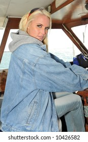 Beautiful blonde at the wheel of a motorboat