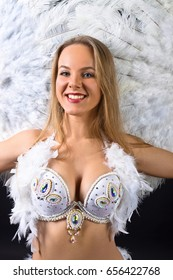 Beautiful blonde in white belly dancer costume with natural feathers and rhinestones . Woman with white fan . Beautiful professional make-up .