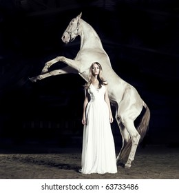 Beautiful blonde in white dress and white horse in rack