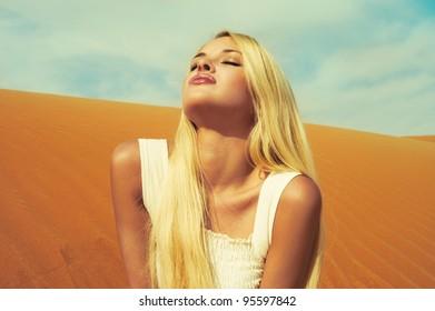 Beautiful blonde in white dress in orange desert. UAE