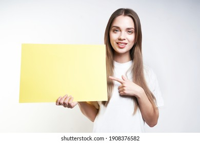 A beautiful blonde in a white T-shirt on a gray background holds a yellow sign. High quality photo