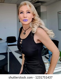 A beautiful blonde white woman in a little black dress and neon purple lips (lavender, lilac) in the office working cabinet