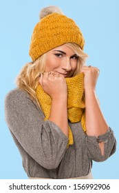 Beautiful blonde who is wearing a knitted yellow hat and a scarf over a blue background