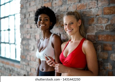 Beautiful blonde woman and Afro woman smiling in fitness outfit.