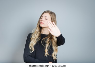 beautiful blonde woman is angry and offended, isolated over gray background