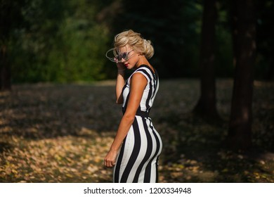 beautiful blonde woman in the autumn forest at sunset