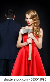 Beautiful blonde woman with ax near the man in suit.  The concept of treason, a family quarrel, murder