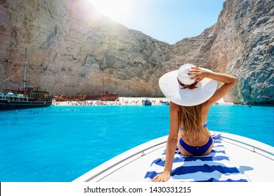Beautiful, blonde woman in a bikini on a boat enjoys the view to the famous shipwreck beach, Navagio, in the island of Zakynthos, Greece