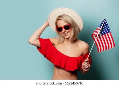 Beautiful blonde woman in bikini with USA flag on cyan background