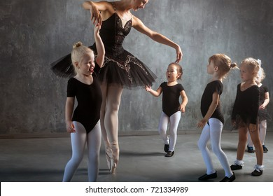 A beautiful blonde woman in a black dance tutu, white pantyhose and pointe shoes is dancing and teaches young girls to dance ballet in a dark studio