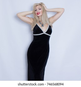 Beautiful blonde woman in black evening dress posing on grey background. Girl with black necklace