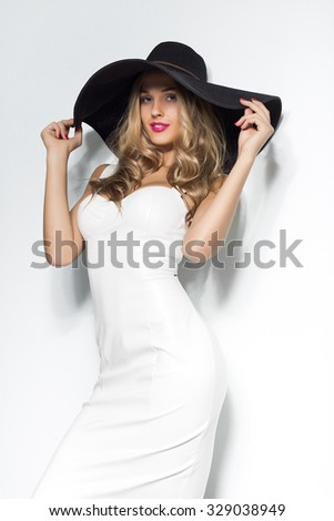 Beautiful blonde woman in black hat and white elegant evening dress posing  on isolated background.Fashion look.Stylish clothing.Studio shot - Image 4b10f8757f2a