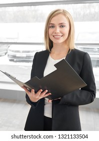 Beautiful blonde woman in black jacket, looking at camera, smiling and posing in showroom of car dealership. Car dealer or manager of car center standing, holding black folder.