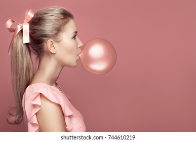 Beautiful blonde woman blowing gum. Fashion portrait on pink background.