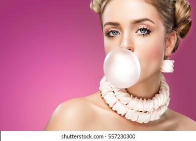 Beautiful blonde woman blowing pink bubble gum. Fashion portrait.