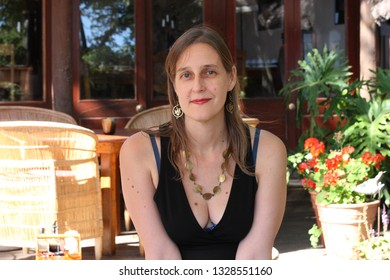 beautiful blonde woman with blue eyes wearing black top, golden earrings and necklace, sitting on a terrace, South Africa