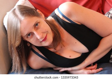 beautiful blonde woman with blue eyes wearing black top, lying on a couch, South Africa